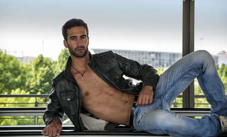 Handsome bearded young man leaning, wearing leather jacket on naked torso, outdoors in urban environment