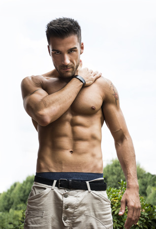 Handsome shirtless muscular young man outdoor, looking at camera
