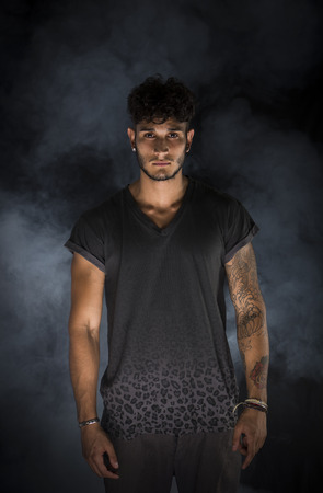 Portrait of handsome young man in dark t-shirt on black background. Dramatic lighting with smoke
