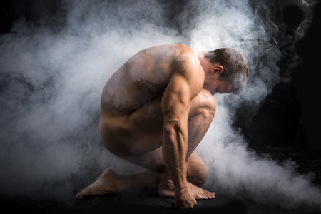 Photo pour Nude Profile of Young Muscle Man Crouching in Fog in Studio with Black Background - image libre de droit