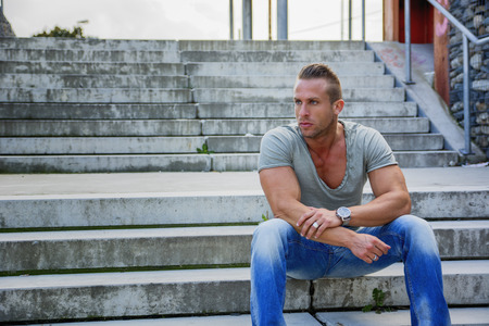 Handsome muscular blond man sitting on stair steps in city setting looking away
