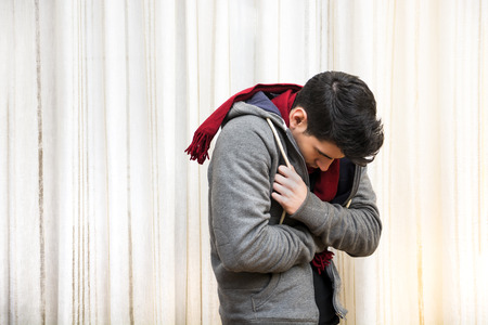 Young man feeling very cold, curling up inside his heavy sweater, wearing a red scarf