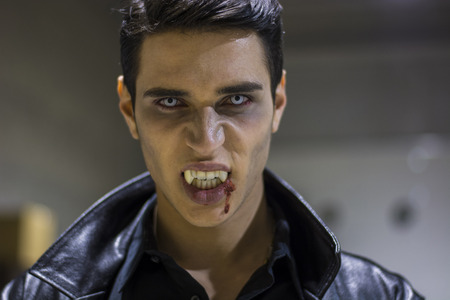 Close up Face of a Handsome Vampire Man in Leather Clothing, with Blood on his Mouth, Looking at the Camera.の写真素材