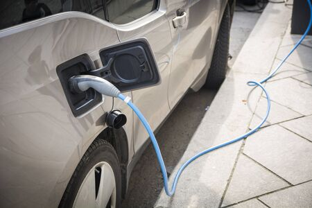 Charging an electric car at a roadside urban charging station showing a close up of the attached connector and cable in a green energy concept