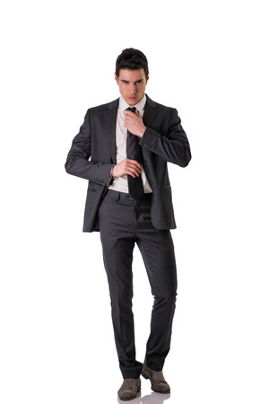 Photo pour Full figure shot of handsome elegant young man with suit and neck-tie, isolated on white, looking at camera - image libre de droit