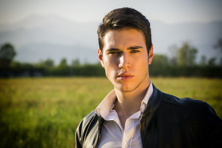 Photo pour Handsome young man at countryside, in front of field or grassland, wearing white shirt and jacket, looking at camera - image libre de droit