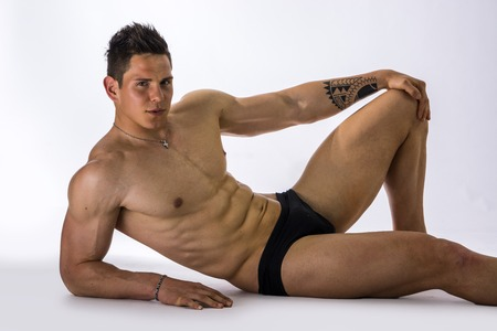 Photo pour Handsome young bodybuilder laying down on the floor, showing ripped abs, muscular pecs, arms - image libre de droit