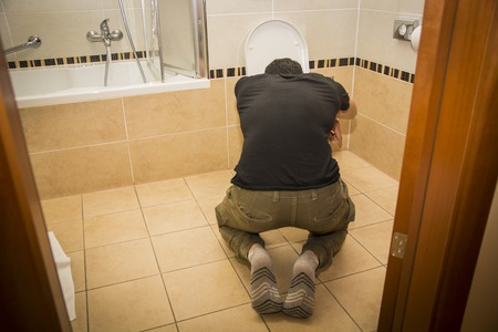 Rear View of a Drunk Young Man Vomiting in the Toilet at Home While in Kneeling Position.