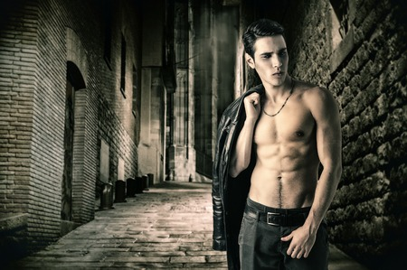 Photo pour Portrait of a Young Vampire Man in an Open Black Leather Jacket, Showing his Chest and Abs, Looking to Right, on Dark Background. - image libre de droit