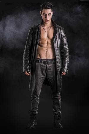 Photo pour Portrait of a Young Vampire Man in an Open Black Leather Jacket, Showing his Chest and Abs, Looking at the Camera, on Black Background. - image libre de droit