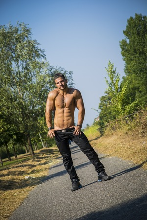 Attractive bodybuilder shirtless outdoor showing torso muscles, abs, pecs and arms, looking at camera in tilted photo