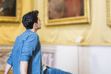 Photo pour Half Body Shot of a Thoughtful Handsome Young Man, Looking At Painting Sitting on Bench Inside a Museum - image libre de droit