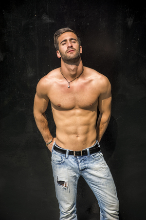 Handsome unshaven shirtless young man standing against black wall, looking at camera