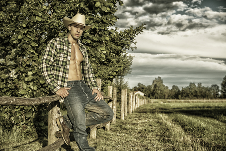 Photo pour Portrait of sexy farmer or cowboy in hat looking at camera while leaning on wooden fence in countryside - image libre de droit