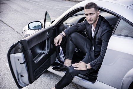 Foto de Portrait of young attractiave man in business suit sitting in his new stylish polished car outdoor - Imagen libre de derechos