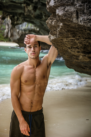 Half body shot of a handsome young man standing on a beach in Phuket Island, Thailand, shirtless wearing boxer shorts, showing muscular fit body, looking at camera