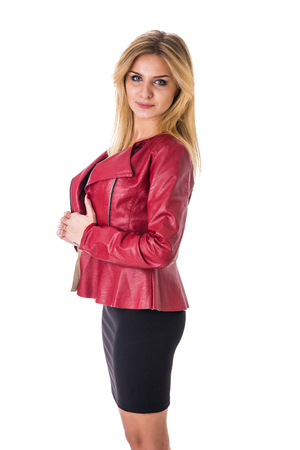 Photo pour Portrait of attractive blonde woman in black skirt and red leather jacket looking at camera in studio shot, isolated on white background - image libre de droit