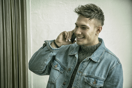 Handsome white asian young man wearing blue denim jacket, talking on the phone and smiling, standing on light background against wall in studio shot