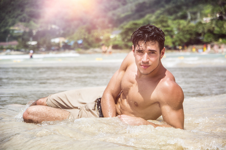 Handsome young man laying down on a beach in Phuket Island, Thailand, shirtless wearing boxer shorts, showing muscular fit body, looking at camera