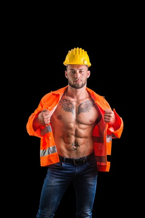 Handsome young muscular construction worker with orange suit open on naked torso, isolated on black background in studio