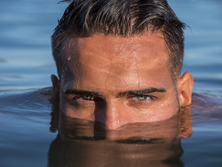 Photo for Attractive young shirtless athletic man standing in water in sea or lake, with half face submerged underwater, looking at camera - Royalty Free Image
