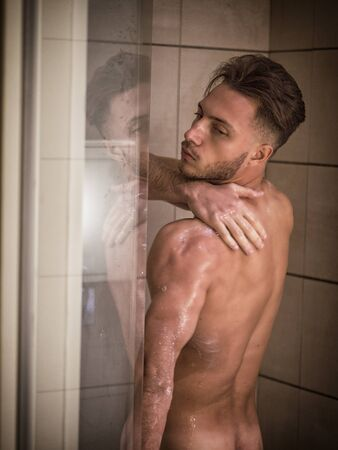 Photo pour Naked Athletic Young Man Taking Shower in the Bathroom to Refresh While Leaning Against Glass Door, Covering Groin with Hand - image libre de droit