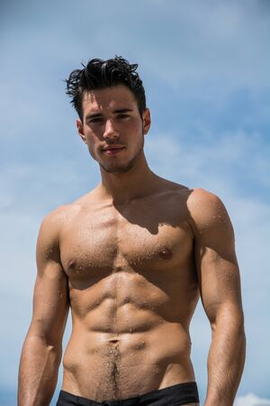 Photo pour Young fit athletic man at beach in summer day showing muscular torso, looking at camera - image libre de droit