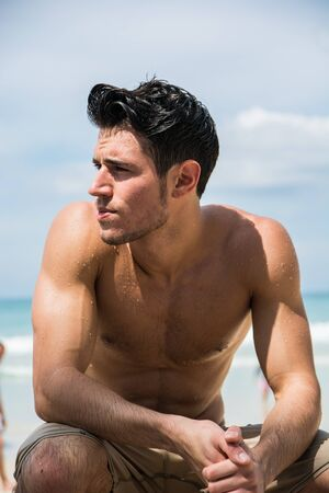 Photo pour Young fit athletic man at beach in summer day showing muscular torso - image libre de droit