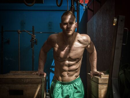 Photo for Handsome muscular young man standing in gym during workout, looking at camera - Royalty Free Image