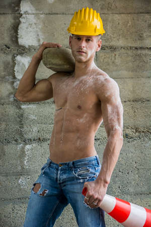 Photo for Sexy, muscular construction worker shirtless, working outdoor, wearing blue jeans and yellow hard-hat - Royalty Free Image