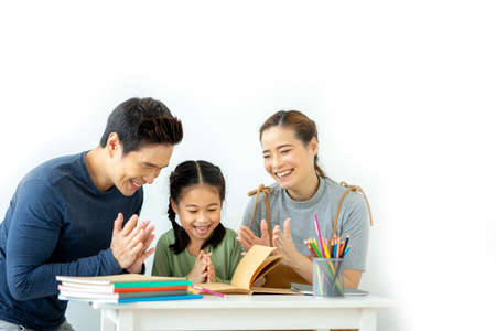 Photo for Asian young mother and father with little daughter sit at desk learning and making homework spending free time together at home. Education concept. - Royalty Free Image