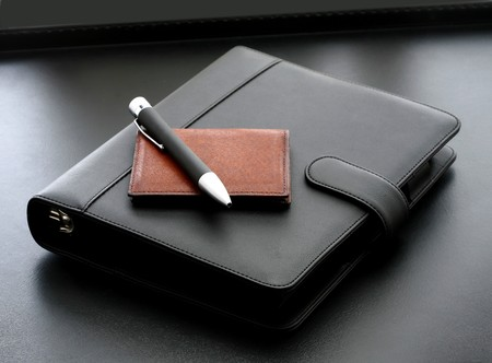 A diary on a desk with a pen and a wallet