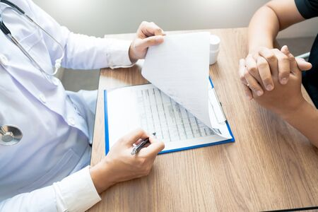 Foto de Doctor explaining and giving a consultation to a patient medical informations and diagnosis about the treatment for condition in hospital, medical ethics concept - Imagen libre de derechos