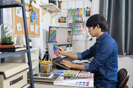 Young Asian man business owner working at home Start up for Business Online, working with laptop for checking, packaging delivery online market on purchase orders to customer, e-commerce concept