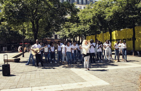 PARIS - JULY, 2016: Middle age woman sings with a chorus of young African French teenagers near Les Halles station in Paris. African male plays a guitar.