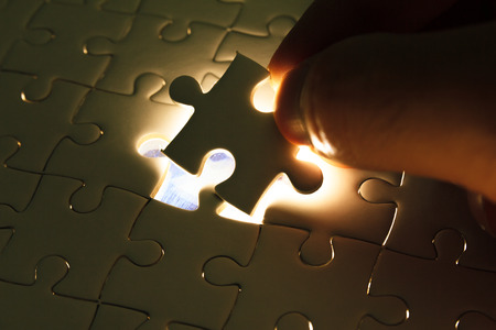 Photo pour Hand insert missing jigsaw puzzle piece with light glow, business concept for completing the final puzzle piece - image libre de droit