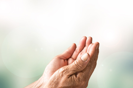 Two open empty hands of old woman with blur background