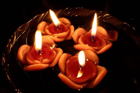 A view of floating rose candles in a bowl of water, lit on the occasion of Diwali festival in India. Focus on 1 rose candle flame.