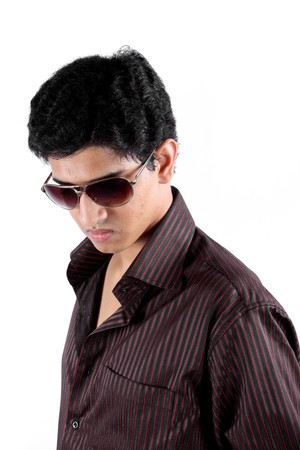 A portrait of a handsome Indian teenager wearing sunglasses, on white studio background.の写真素材
