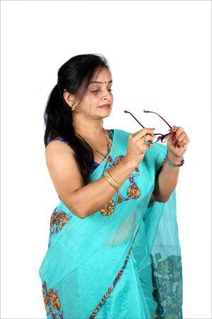 Foto de A beautiful Indian middleaged woman wearing her glasses, on white studio background. - Imagen libre de derechos