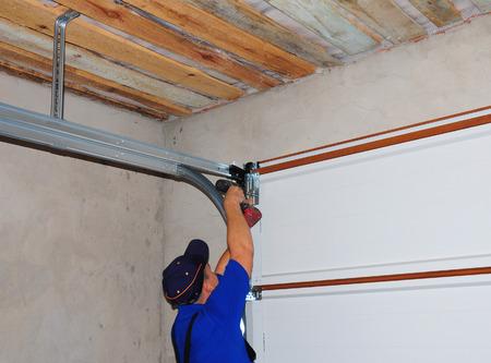 Contractor Installing Garage Door Post Rail and Spring Installation and Garage Ceiling. Spring Tension Lifts Metal Section Garage Door Panel that the Motor does not have to Lift Entire Weight.