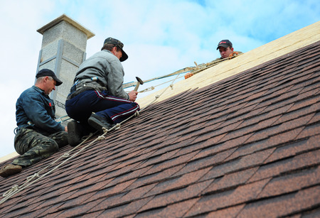 KIEV - UKRAINE, October - 09, 2017: Roofing Construction. Roofing Contractors Install New House Roofing with Asphalt Shingles Roofing Construction. Roofers with safety rope. Roofing Contractor.