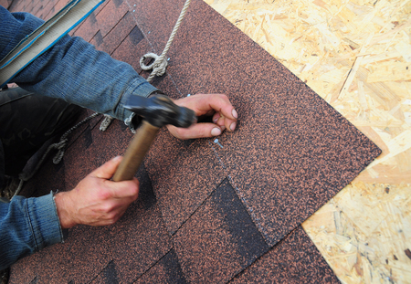 Foto de Roofer Install Asphalt Roof Shingles. Close up view on Roofer Installation  Asphalt Roofing Shingles Installation. Roofing Construction, Roofer Roofing Repair. - Imagen libre de derechos