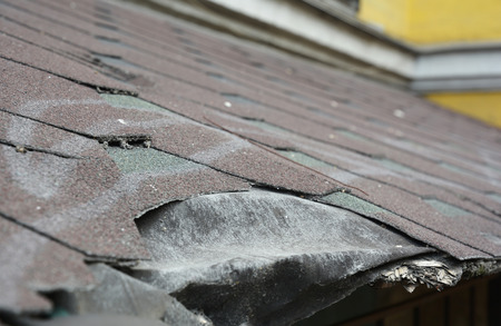 Photo pour Asphalt shingles damage. Roofing shingles asphalt. Fixing damaged roof shingles. - image libre de droit