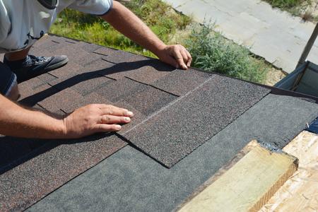 Foto de Roofer installing asphalt shingles on house construction roof corner. Roofing construction. Roofing contractor install roof tiles. - Imagen libre de derechos