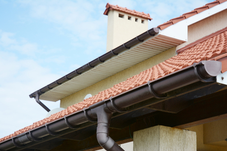 Photo for Rain gutters system  on new house with chimney, red clay tiled roof and gable and valley type of roof construction - Royalty Free Image