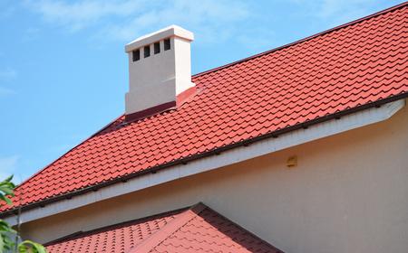 Photo pour Metal house roof with chimney and soffit boards. - image libre de droit