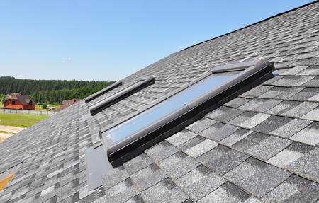 Photo pour Skylights windows on modern house roof top.  Attic skylight windows on asphalt shingles roof. - image libre de droit