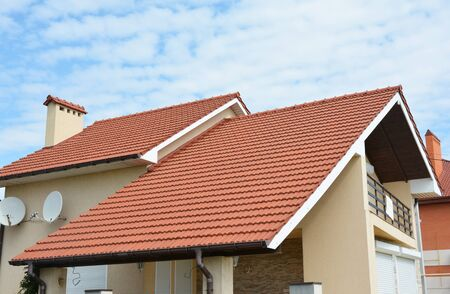 Photo pour Modern house with red clay tiled rooftop, balcony, roof gutters, chimney. Valley and gable type of roof. - image libre de droit