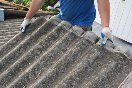 Foto de Asbestos removal roofer roof works. House with old, danger asbestos roof tiles repair and renovation.  Risks of Asbestos Roofs, Asbestos Roof Removal. - Imagen libre de derechos